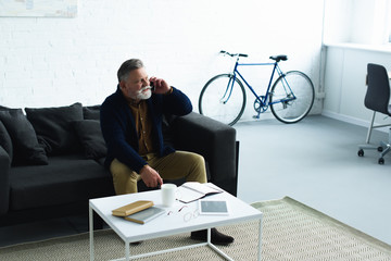 bearded senior man talking by smartphone while sitting on sofa and looking away at home