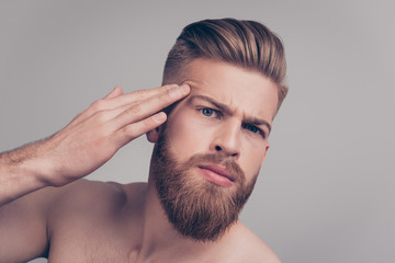 Close up portrait of disturbed sad unhappy handsome unsatisfied neat upset groomed nervous scared brutal macho looking for pimples on his face touching with fingers isolated on gray background