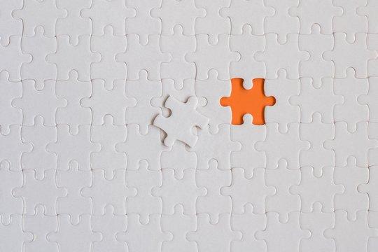 White details of jigsaw puzzle on orange background