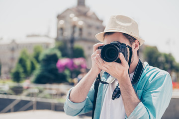 Portrait of handsome focused interested delightful creative professional successful stylish fashionable trendy fashion photographer wearing casual outfit taking photo of european old city