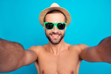 Self portrait of cheerful bachelor, stylish, funny guy, ladies' man in glasses and hat on holidays shooting selfie over blue background