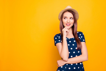 Portraitwith copy space of charming, pretty, thoughtful, sexy, professional woman in polka-dot outfit holding hand on chin, looking at empty place with eyes, standing over yellow background