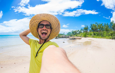 Happy handsome man taking a selfie at holiday on a tropical island at summertime.