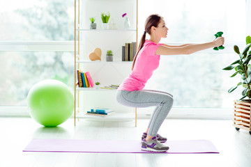Profile view photo of focused strong concentrated enduring beautiful gorgeous stylish trendy girl dressed tight leggings casual tshirt doing sit-ups holding green dumbbells in hands white light room