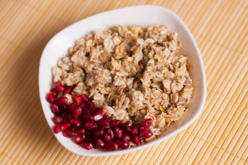 Cooked yummy warm oatmeal and heap of ripe fresh pomegranate seeds in white ceramic bowl on clean bamboo rug
