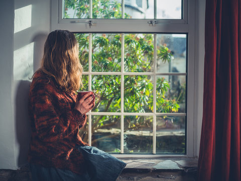 Young woman drinking tea by the window