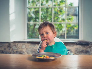 Cute little baby having his dinner at the table