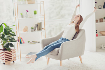 Hotel teenager jeans living-room window casual pleasure delight concept. Nice beautiful calm relaxed girl lying sitting in beige armchair stretching legs and arms wearing white sweater denim trousers