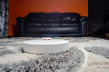 Robot vacuum cleaner on carpet, Smart robotic automate wireless cleaning technology machine in room.