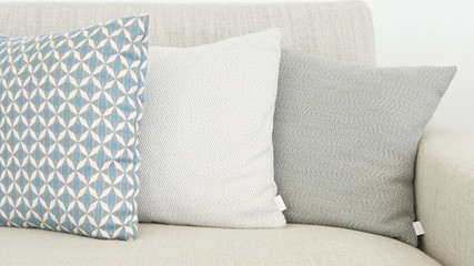 Close-up of three different sizes cushions in soft, pastel colors, almost monochrome, positioned on a beige, textile sofa, very modern, minimalist interior design detail for a cozy home