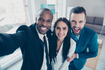 Self portrait of stylish successful, professional trio, afro-american black man with stubble shooting selfie with hand on smart phone with friends, together standing in work place, station