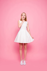 Vertical full-length portrait of sweet charming nice excited cheerful lovely romantic trustful impressed reaction rejoicing girl wearing cocktail dress touching the bottom isolated on background