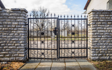 wrought iron fence gate and cut stone fence