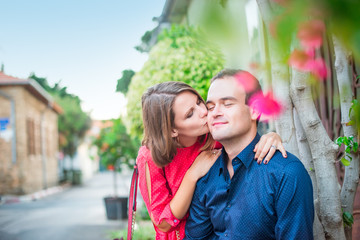Young woman kissing a man on cheek. Fall in love romantic married couple in bright clothes on the street with blooming trees. Family happiness concept. Soft selective focus. Copy space.