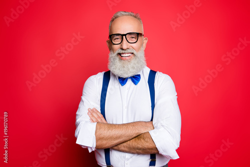 0b71b1c977bc ... cool, old man with beaming smile having his arms crossed, looking at  camera, wearing blue bow-tie and suspenders, isolated on red background