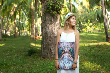 A woman artist stands under palm trees with a picture in her hands. Phangan, Thailand.