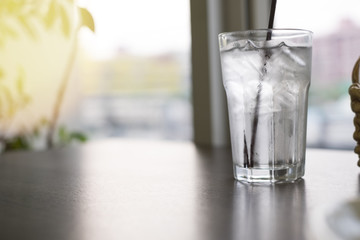 Glasses of water on a wooden table. Selective focus with straw. With light effects.