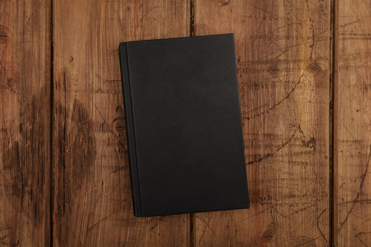 An overhead photo mockup of a black book with a place for text