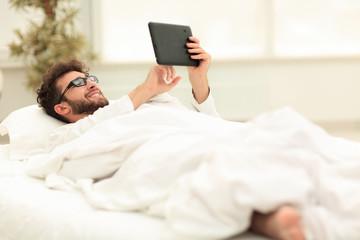 closeup.sleepy man looking at the screen of a digital tablet.