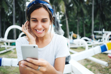 Young beautiful woman near the ocean, smiling and using mobile phone