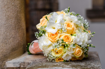 Bouquet of flowers of the bride. A wedding bouquet of flowers lies on the old balcony of the castle. Bouquet of flowers of peach-colored roses, eustomises.