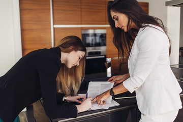 Female realtor and customer signing residential contract for sale and purchase standing in kitchen of new apartment