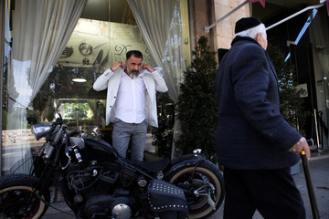 Israeli hair designer Doron Bar, 42, stands next to his motorcycle in front of his hair saloon, near Jerusalem's Old City
