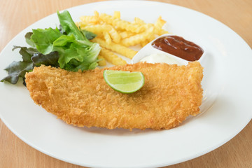 Fried fish and French fries served with vegetables on a white plate.