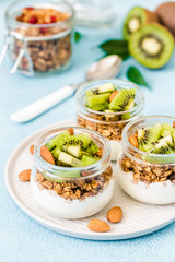 Fruit dessert, kiwi granola parfait with nuts and greek yogurt in glass jars. Selective focus, space for text.