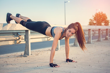 Fit young woman doing push ups over bridge's fence outdoors.