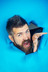 Screaming man looking through hole in paper wall. Bearded man shouting loudly through hole in blue paper. Male head and hand making hole in blue paper. Copy space for advertise, to insert text, slogan