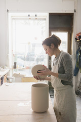 A ceremic artist is putting the finishing touches to a ceramic urn in a ceramic workshop.