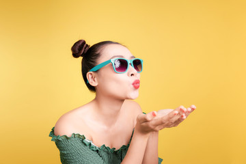 Fashionable asian woman in trendy sunglasses sends a kiss against bright yellow background