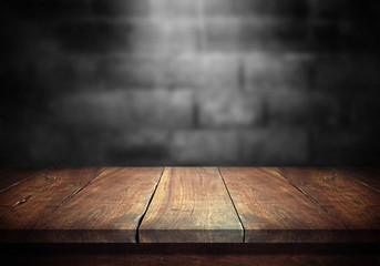 Old wood table with blurred concrete block wall in dark room background. Fototapete