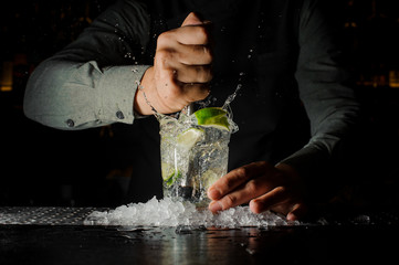 Bartender squeezing juice from fresh lime using citrus press and splashing it out