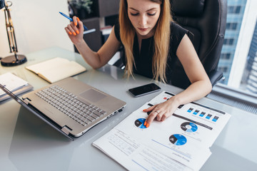 Female businesswoman readind financial report analyzing statistics pointing at pie chart working at her desk