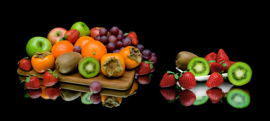 still life of fruit on a black background