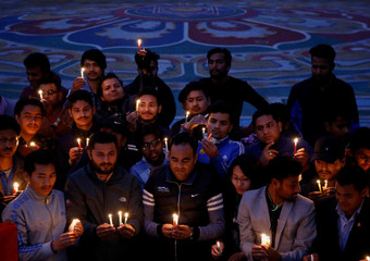 People hold candles during the vigil to pay homage to the victims of US-Bangla airplane crash in Kathmandu