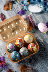 homemade decorated easter eggs in an egg box