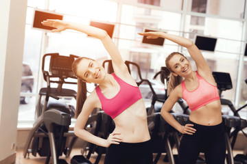 Mother and daughter doing exercises at the gym. They look happy, fashionable and fit.