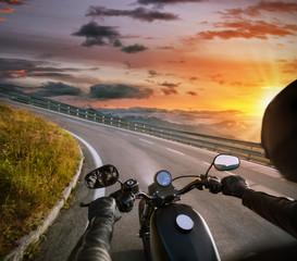 POV of motorbiker holding steering bar, riding in Alps