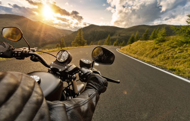 POV of motorbiker holding steering bar, riding in Alps Wall mural