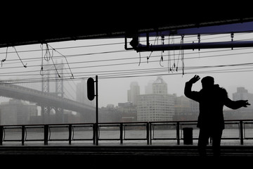 A woman is seen in silhouette dancing beneath the FDR drive underpass  beneath the Manhattan Bridge during a snowstorm in New York