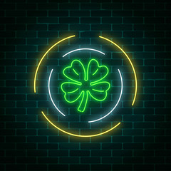 Neon glowing clover leaf sign in circle frames on a dark brick wall background. Green shamrock