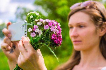 Young woman with a bouquet of flowers uses a phone as a camera
