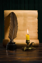 The concept of education and writing, an inkwell with a pen and a candle on the background of a roll of parchment