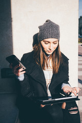 young woman outdoor sitting using tablet  and smart phone- technology, small business, multitasking concept