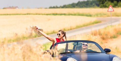 Best friends having summer joyride in convertible car passing a field  Wall mural