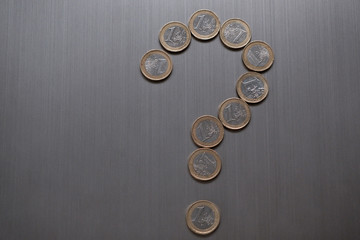 Question mark made of one euro coins on a metallic background. European currency finance concept