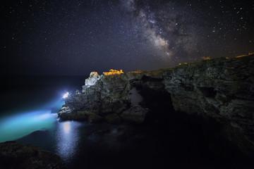 the Milky Way galaxy rising above shore